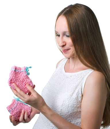 bootees: Portrait of young pregnant women with bootees in hands on white background. Isolation