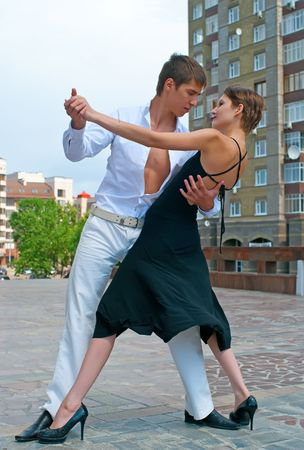 young couple dancing Latino dance against urban landscape Stock Photo - 6808448
