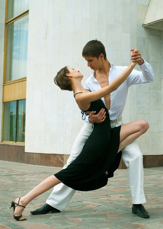 young couple dancing Latino dance against urban landscape Stock Photo - 8434402