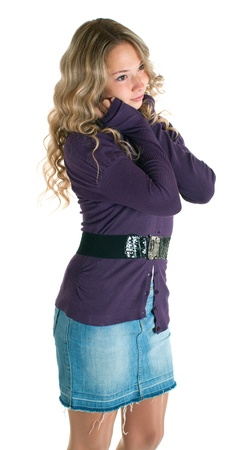 The young beautiful girl in a lilac shirt and jeans skirt. Isolation on a white background photo