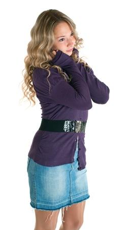 La belle jeune fille dans une jupe de chemise et jeans lilas. Isolement sur un fond blanc
