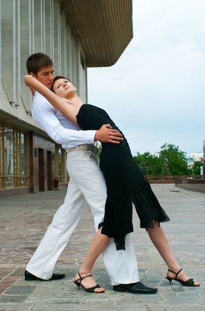 young couple dancing Latino dance against urban landscape  photo