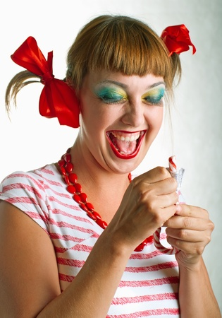 Fun laughing girl with striped candy on light background. Stock Photo - 10106111
