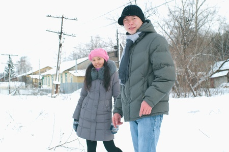Happy smiling young couple against winter landscape