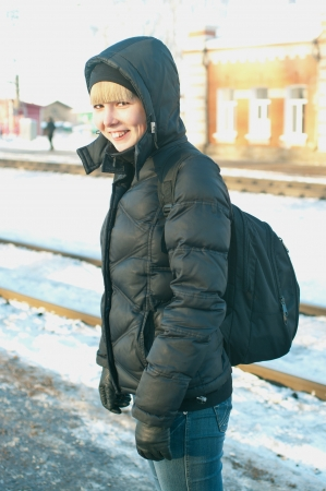 The girl at the station waiting the train against winter