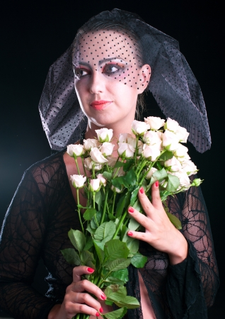 Girl in a black veil with pink roses on black background. Shallow DOF