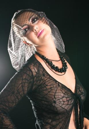 Girl in a black veil on black background. Shallow DOF