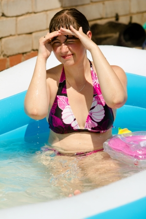 Smiling young girl in the pool in sunny day. Shallow DOF