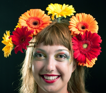 The beautiful girl with a wreath of flowers on her head. On black background