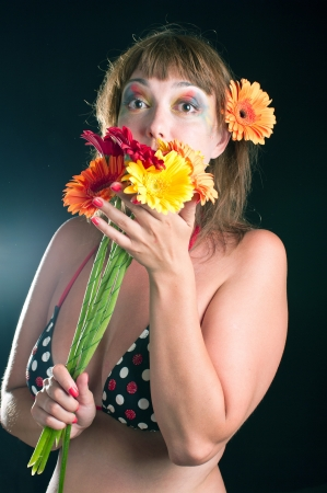 Beautiful adult woman with bouquet of flowers on black background