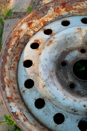 Used old wheel at grass. Shallow DOF Stock Photo - 21377881