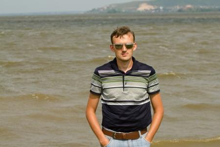 Young men against summer landscape with river Volga