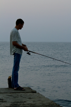 Angler on the sea beach in morning sun. Shallow DOF