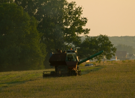 Machine for harvesting in field at evening. Shallow DOF Stock Photo - 23091427