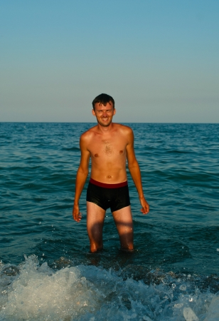 Young guy in water of sea on sky background  Stock Photo