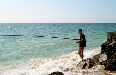 The young men fishing in sea of Azov. Summer landscape