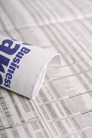 share prices: A rolled up mewspaper with the word business om it, placed over share prices.