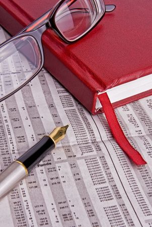 scenarios: A diary, some spectacles and a fountain pen all placed on a financial newspaper. Perfect for use in financial scenarios or business topics.