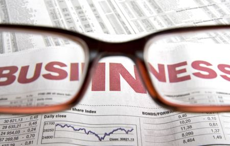 financial newspaper: Looking at a financial newspaper through a pair of spectacles. Perfect for business and finance concepts.