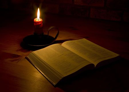 A bible open on a table next to a candle. The light illuminating the bible is only from the candle. Perfect for religion, easter and christmas themes. photo