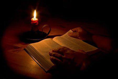 scripture: Reading the bible by candle light. Only light in this image is from the candle. Perfect for religious, eater or christmas themes.