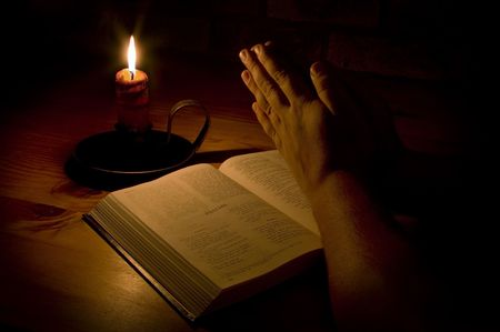 Praying next to the bible by candle light. Only light in this image is from the candle. Perfect for religious, easter or christmas themes photo