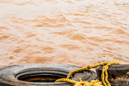 Muddy Waves Hitting a Tyre tied with Yellow Rope, Panshet Dam Stock Photo