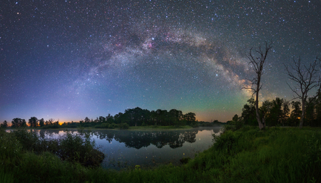 Milky Way arc over a small forest lake Stock Photo