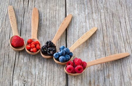 Wooden spoons with forest berries on an old wooden board