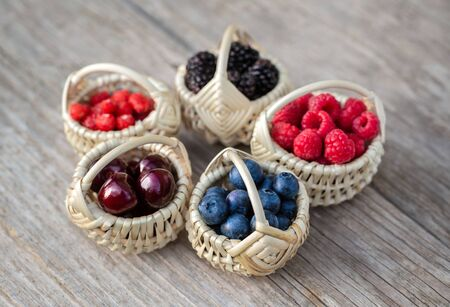 Tiny baskets of berries on old wooden board Archivio Fotografico