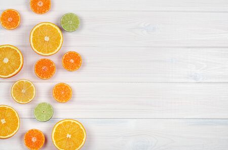Colorful citrus fruits on white wooden