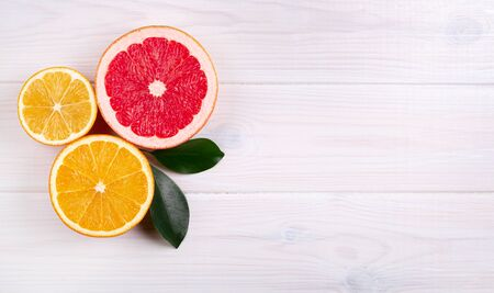 Colorful citrus fruits on white wooden background
