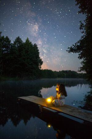 Little girl sitting under starry sky