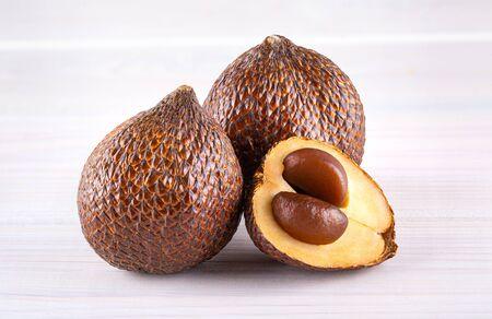 Salak (Salacca zalacca) or Snake fruit isolated on wooden background