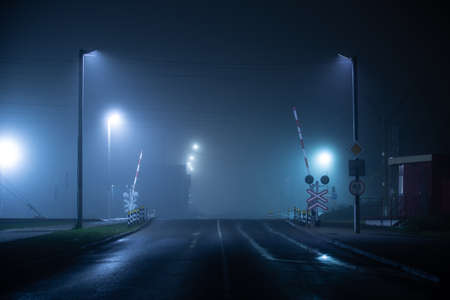 Railways crossing at foggy and wet night Standard-Bild