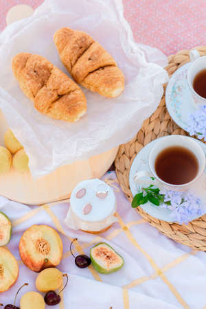 A picnic at dawn in gentle colors. Hot tea, fresh croissants, jam and fruit on a blanket with a wooden stand.