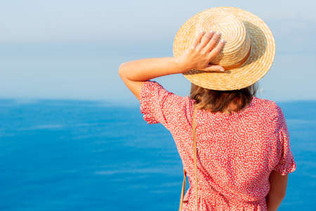 Slavic girl in a hat near the sea on the edge of a cliff.Beautiful advertising vacation.