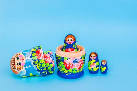 Colorful matryoshka on a blue background, Slavic souvenir.