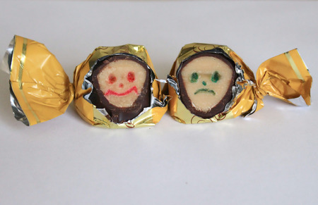 pessimist: on a light background are two candy containing faces two types of optimist and pessimist