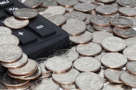 twenty five: pila de veinticinco centavos monedas y una calculadora