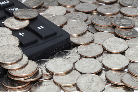 five cents: pile of twenty five cents coins and a calculator