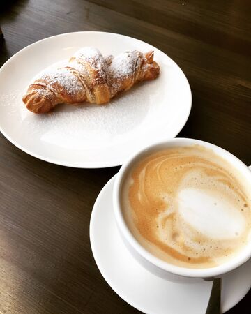 Croissant and coffee on wooden table