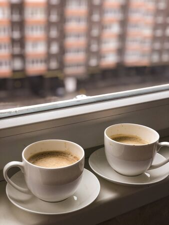 Two white cups coffee on the windowsill