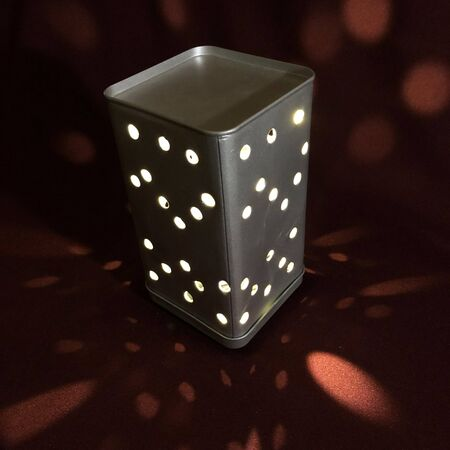 night light in a metal box with holes with a burgundy background Stockfoto