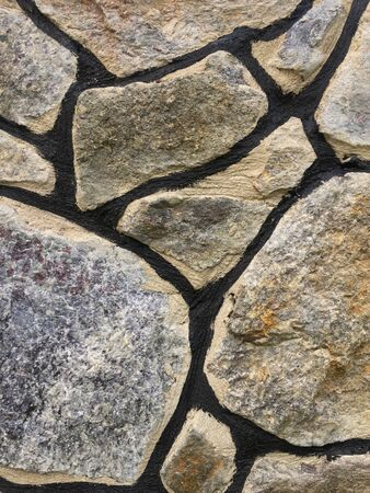 Texture of old stone wall of large boulders.