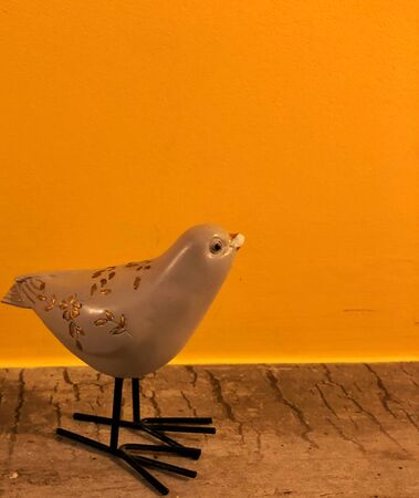 souvenir bird on a orange yellow background with space for text Stockfoto