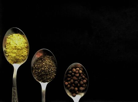 three spoons with spices on black background