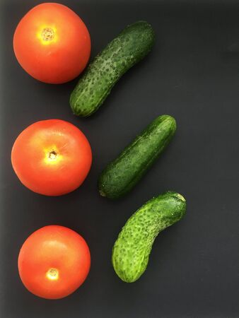 tomatoes and cucumbers on a black background