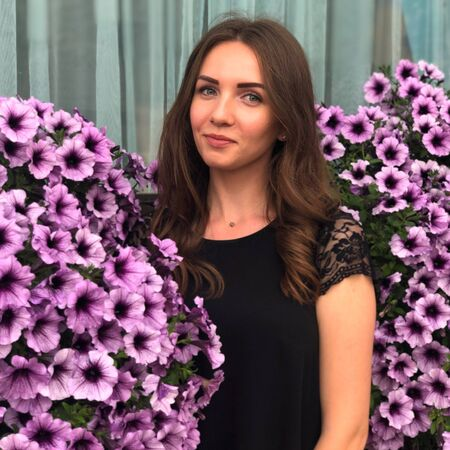 Beautiful Ukrainian girl with curls in a black dress near the bushes of violet petunia Stock fotó