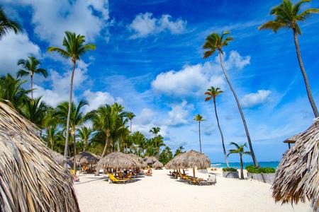 Der weiße Sand des dominikanischen Strandes von Bavaro. Strandwagenaufenthaltsräume unter Palmenschatten und blauem Himmel.